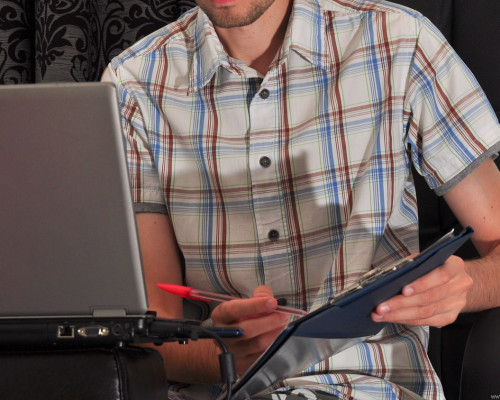 Man in white shirt with a notepad and a laptop